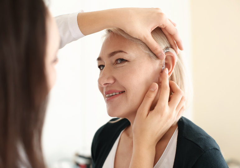 Audiologist fitting a Phonak Hearing Aid
