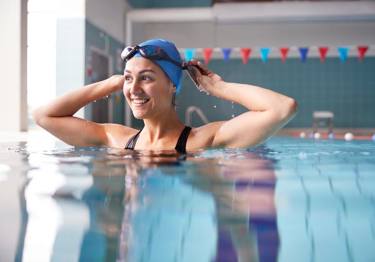 Lady in a pool wearing custom swimming ear plugs
