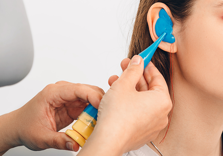 Audiologist taking impressions to mould custom earplugs for swimming
