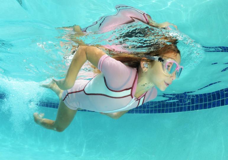 Child wearing custom swimming ear plugs in the pool